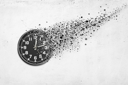 Classic clock on white concrete background disintegrate in a small parts and flying away. Time flying concept