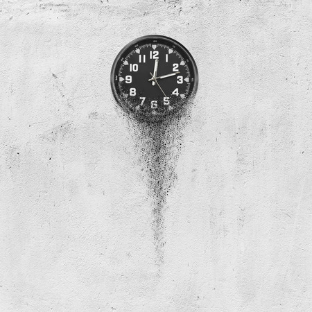 Classic clock on white concrete background disintegrate in a small parts and flowing away. Time flying concept Stock Photo