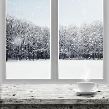 Hete drank in kop op lijst over de winter bosachtergrond door venstermening