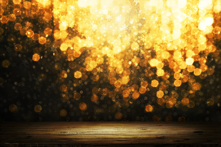 Christmas golden bokeh with snow flakes behind wooden table background