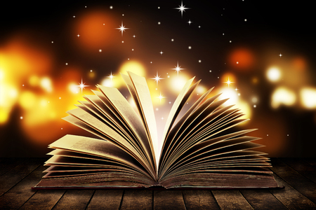 Open book on wooden vintage table with mystic magic bright light on background Stockfoto