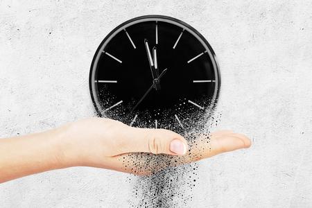 Reloj clásico sobre fondo de hormigón blanco se desintegra en pequeñas partes y fluye. Concepto de vuelo en el tiempo