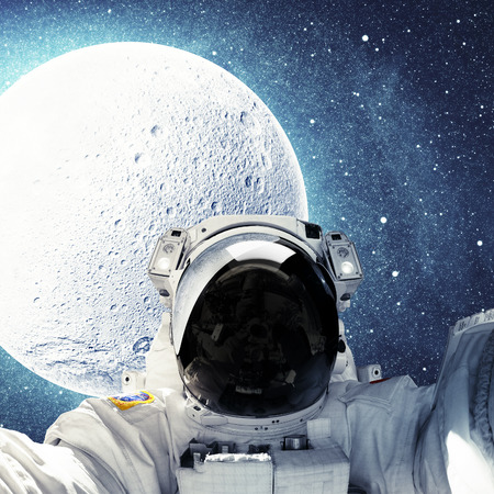 Astronaut over moon in outer space.