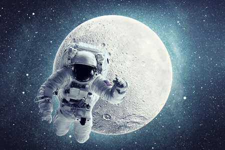 Astronaut in outer space over full moon and stars background. 写真素材