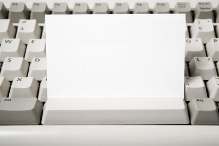 Close up of a computer keyboard and blank business card