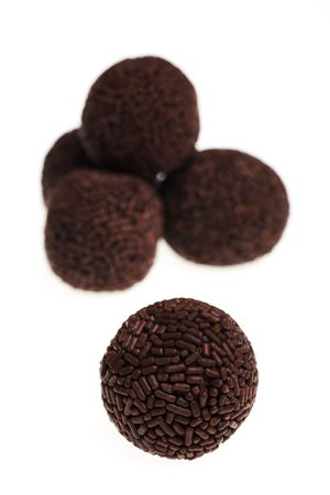 Several assorted chocolate rum truffles isolated on white background