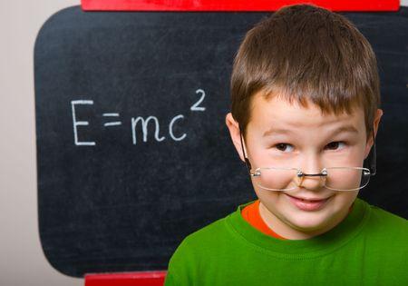 Smiling schoolboy standing at chalkboard