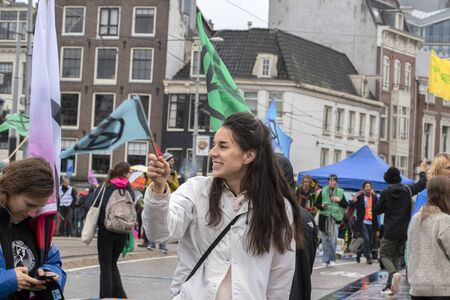 Protester With A Logo On A Flag At The Blauwebrug At The Climate Demonstration From The Extinction Rebellion Group At Amsterdam The Netherlands 2019