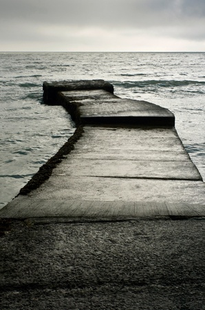 lonliness: a concrete jetty at the end of south beach tenby