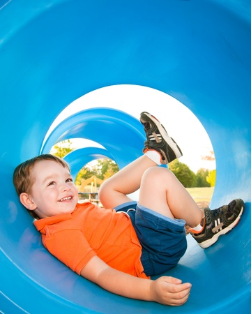 Cute young boy playing in tunnel on playground.
