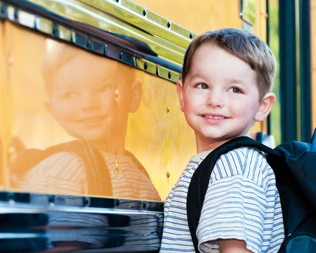 school backpack: Young boy with nervous smile waits to board bus on first day of school.