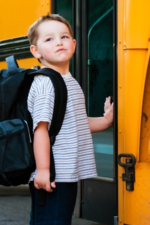 pre school: Defiant young boy in front of yellow school bus waiting to board on first day back to school