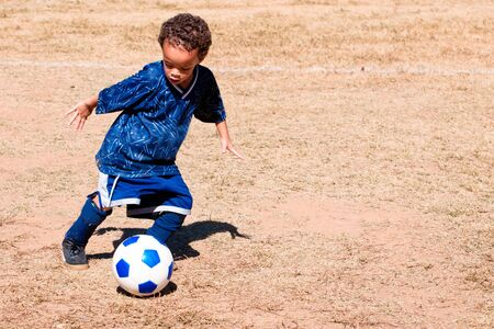 children at play: Young African American boy playing soccer.