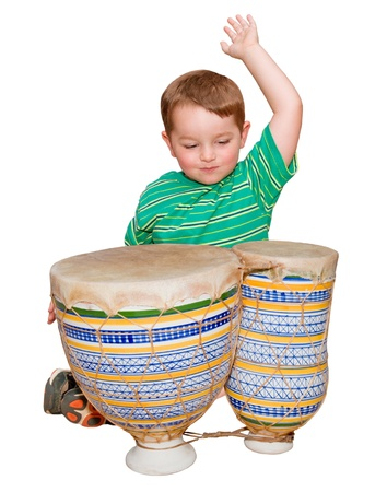 Young boy plays African bongo tom-tom drums, isolated on white background  Stock Photo