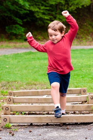 Young boy jumping over obstacle on exercise trail