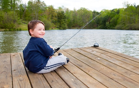 Boy smiles while fishing from dock on lake.  photo
