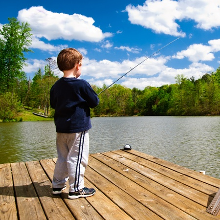 boating: Boy fishing from dock on lake.  Stock Photo