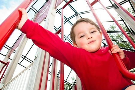 obesidad infantil: Ni�o jugando en el patio de juegos durante la primavera.