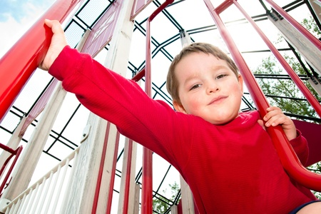 Young boy playing on playground during spring.  Stock Photo
