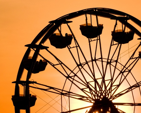 wheel spin: Silhouette of ferris wheel at sunset at county fair.