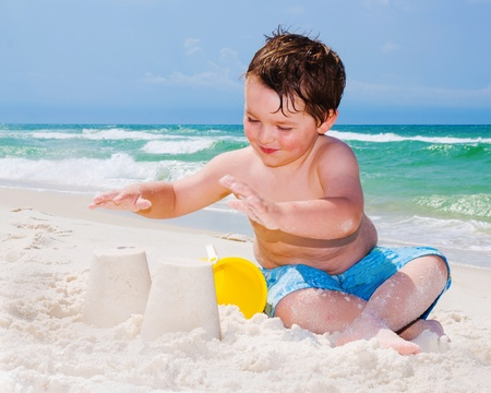 Young boy builds sand castle while playing on beach.