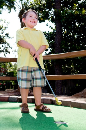 Young boy smiles while playing mini golf on putt putt course.  photo
