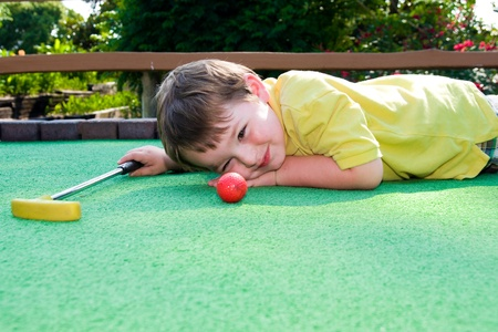 mini: Young boy plays mini golf on putt putt course. Stock Photo