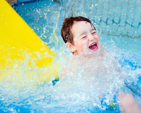 Boy splashes down after riding water slide Stock Photo