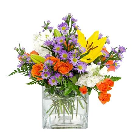 arreglo floral: Flores de colores central arreglo en florero de cristal cuadrada con rosas, margaritas y llilies aislado en blanco Foto de archivo