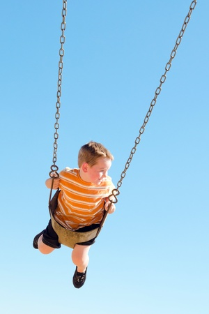 Cute young boy swings at kid park playground  Stock Photo - 10436226