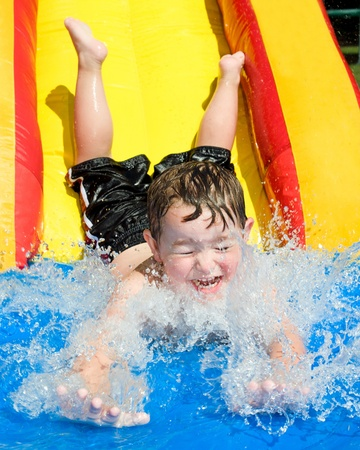 Young boy or kid has fun splashing into pool after going down water slide during summer