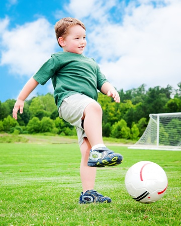 run down: Young boy or kid plays soccer or football sports for exercise and activity.