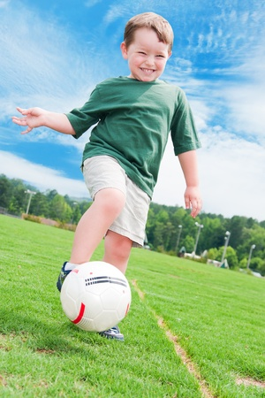 Young boy or kid plays soccer or football sports for exercise and activity.  photo