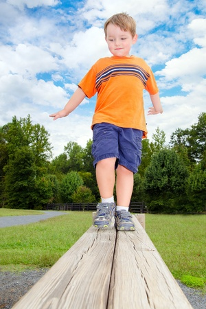 Young boy or kid balancing on beam obstacle on exercise trail outdoors at park Stock Photo