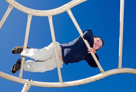 obesidad infantil: Chico joven arrastrándose sobre barras en el patio de