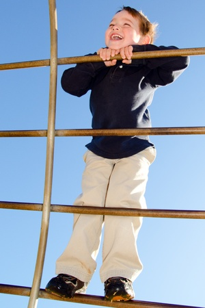 obesidad infantil: Chico joven arrastrándose sobre barras en el patio