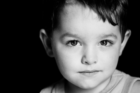 Monochrome portrait of young boy with serious expression photo
