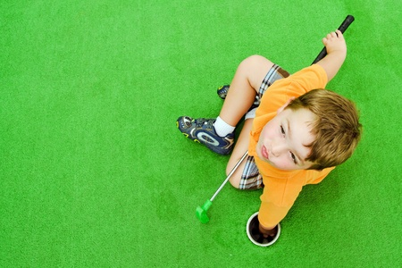Young boy pulling ball out of hole while playing miniature golf  photo