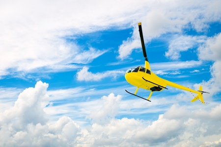 airborne: Yellow helicopter flying with cloudy blue sky background
