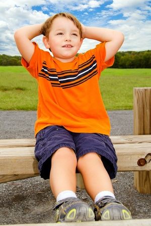 situps: Young boy does sit-ups while exercising outdoors at playground. Stock Photo