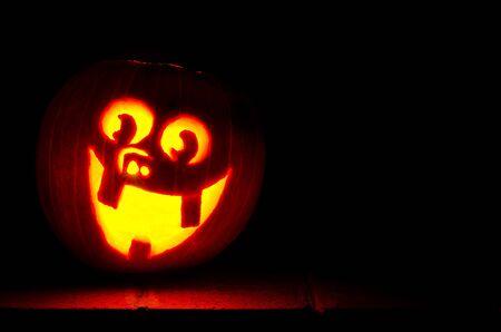 stoop: Carved happy jack-o-lantern on stoop at night.  Stock Photo