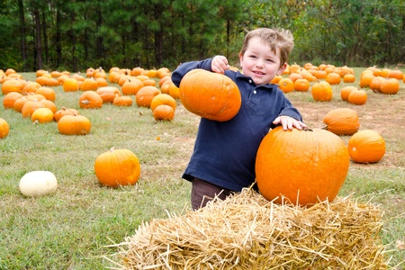 Happy young boy picking a pumpkin for Halloween  Foto de archivo