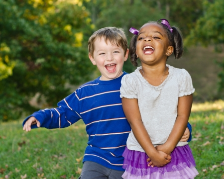 Young African-American girl and young white boy playing together in park
