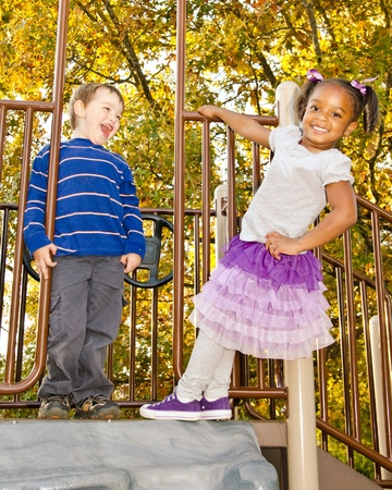 amusement park black and white: Young African-American girl and young white boy playing together in park