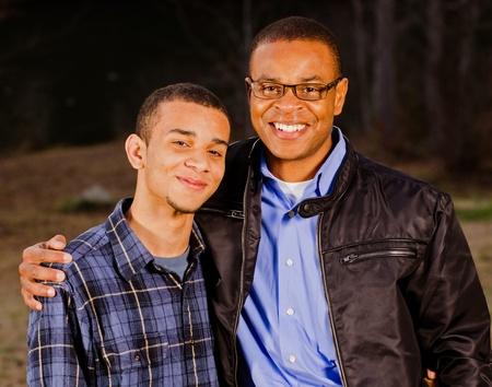 アフリカ系アメリカ人の父と屋外公園で 10 代の息子の肖像画