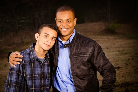 Portrait of African-American father and teenage son outdoors at park  photo