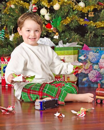 christmas morning: Young boy unwrapping presents on Christmas morning