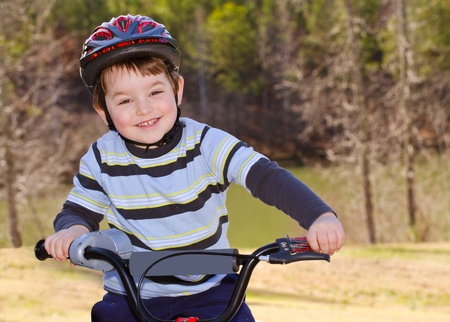 crash helmet: Boy riding bike with safety helmet outdoors at park  Stock Photo