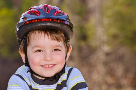 Boy riding bike with safety helmet outdoors at park  photo