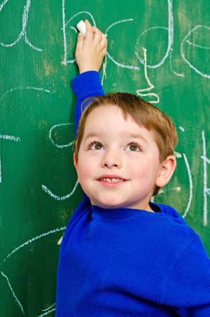 grade schooler: Young boy writing on chalkboard